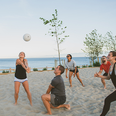 People playing volleyball by the beach